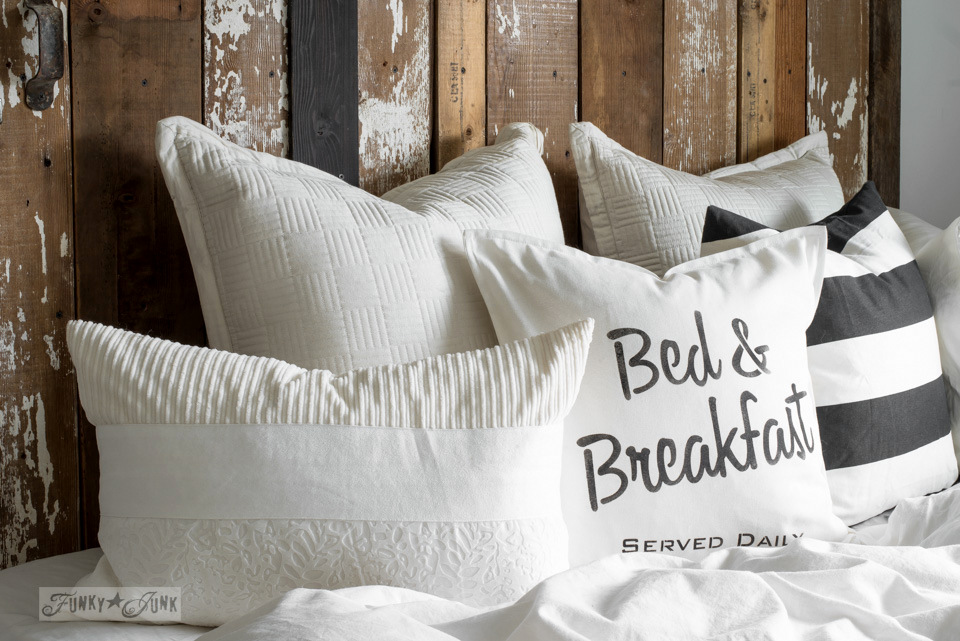 Learn how to make this cheater reclaimed wood barn door headboard with faux hardware, with a Bed & Breakfast DIY pillow, made with Funky Junk's Old Sign Stencils!