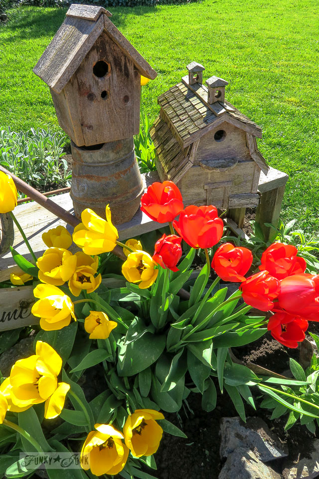 A small and easy blooming tulip birdhouse garden vignette in shades of vibrant yellow and red and barn wood birdhouses | funkyjunkinteriors.net