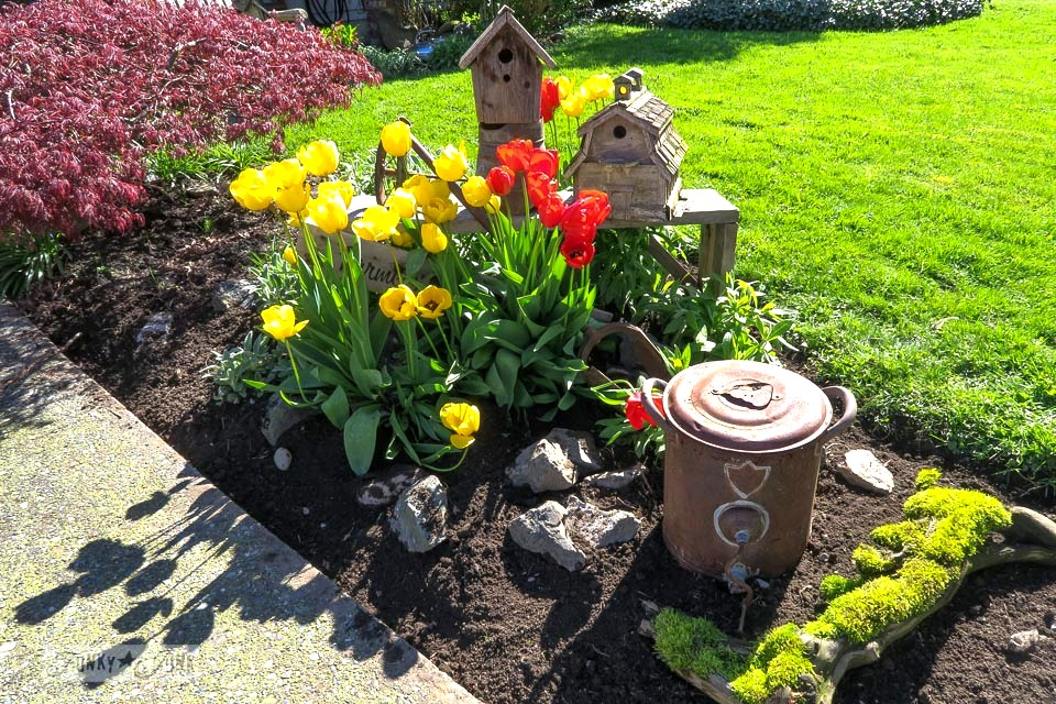 A blooming tulip birdhouse garden with vivid red and yellow, with garden junk and a moss covered log | funkyjunkinteriors.net