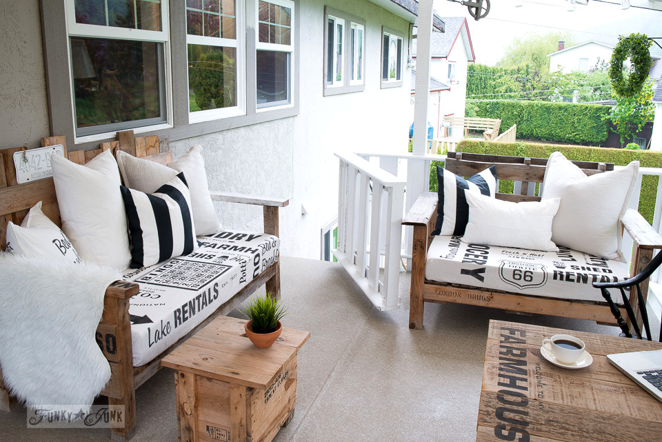 Rustic patio decor with old windows, pallet wood furniture with stenciled fabric, and antique oars, with a little farmhouse styled side table | funkyjunkinteriors.net