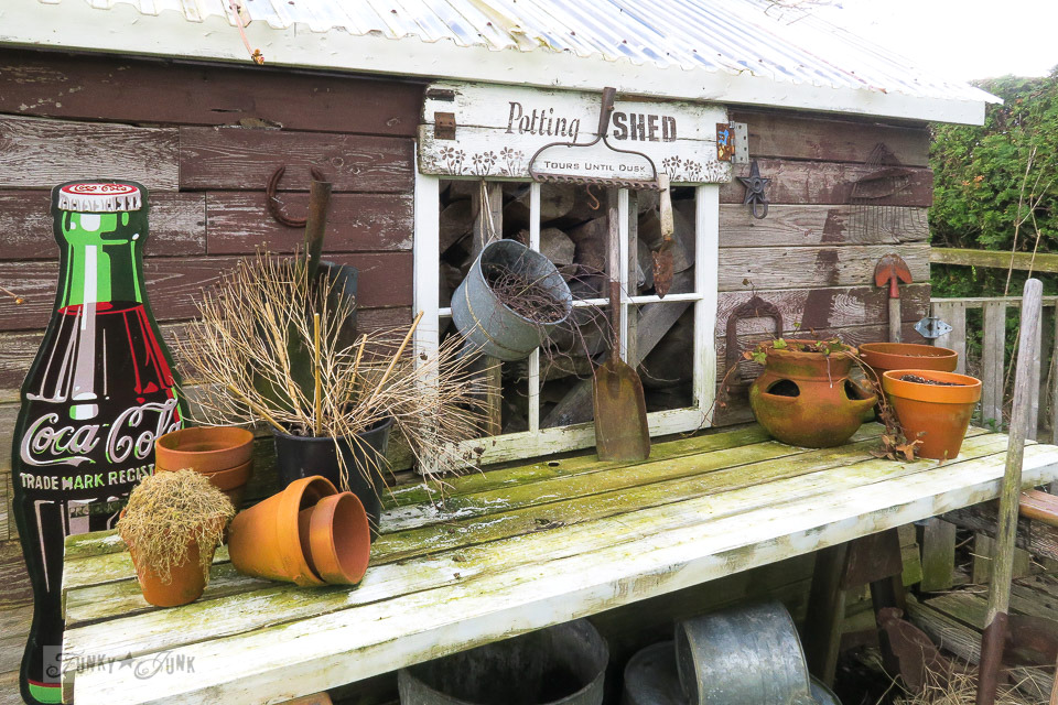 clay pots and dead plants and a potting shed that needs pressure washing