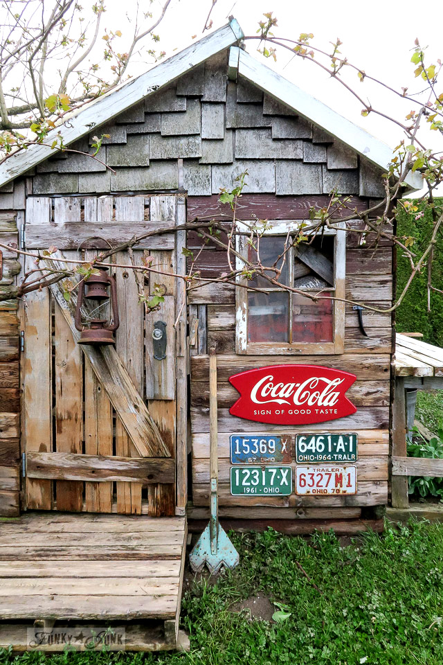 Pressure washing the grape vine covered rustic garden shed for spring | funkyjunkinteriors.net