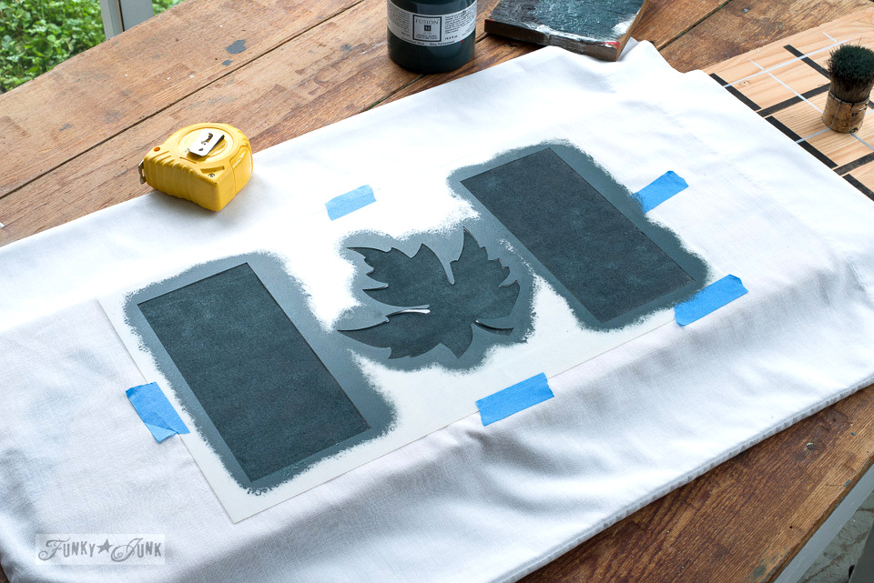 A plain white pillow case gets stenciled with Muddaritaville Studio's Canadian Flag and Funky Junk's Old Sign Stencils Buffalo Check, using Fusion Mineral Paint's Homestead Blue and Coal Black | funkyjunkinteriors.net