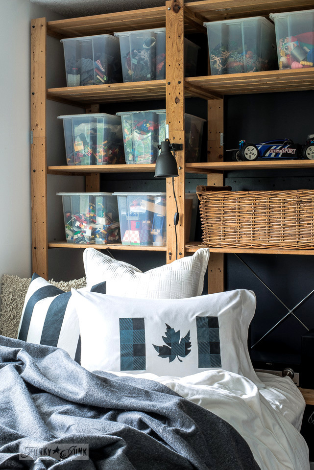 A blue and black Buffalo Checked Canadian Flag pillow in a teen's room, including a black wall with wood shelving toy storage. Pillow layered with Funky Junk's Old Sign Stencils, Muddaritaville Studio and Fusion Mineral Paint | funkyjunkinteriors.net