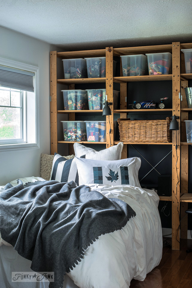 Cozy boy's bedroom with floor to ceiling shelving storage for a headboard, hanging closet blue doors, a buffalo checked Canadian flag pillow and a sitting area | funkyjunkinteriors.net