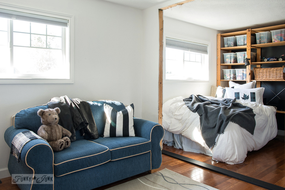 Cozy boy's bedroom with floor to ceiling shelving storage for a headboard, hanging closet blue doors, and a sitting area | funkyjunkinteriors.net