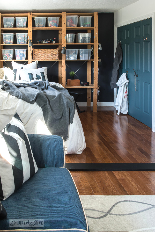 Cozy boy's bedroom with floor to ceiling shelving storage for a headboard, hanging closet Homestead Blue doors by Fusion Mineral Paint, and a sitting area | funkyjunkinteriors.net
