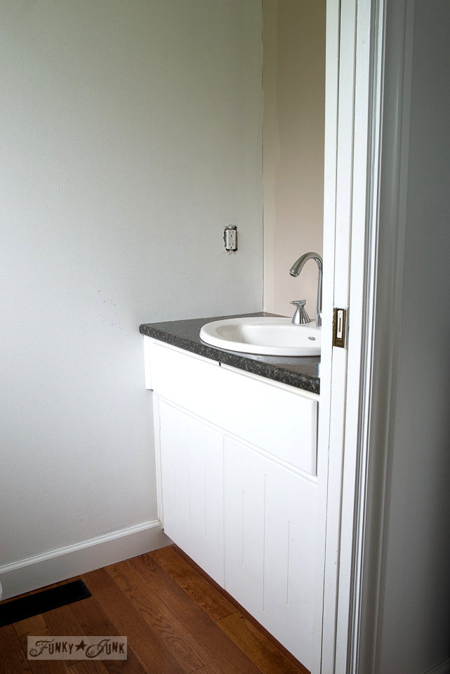 Hanging up a white bathroom vanity door in a small ensuite.
