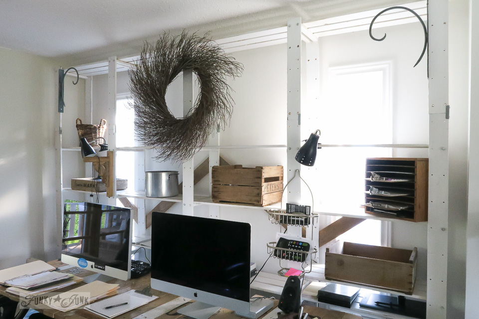 Floor to ceiling white office storage shelving in a blog office, decorated with a huge twig wreath.