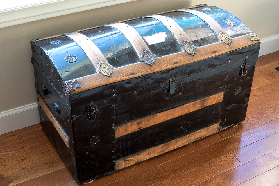 Wood strapped black metal antique trunk.