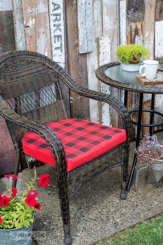 How to Buffalo Check plain red cushions for a cabin inspired outdoor table and chairs. This post showcases a patio set up as well as a bistro area against a unique reclaimed wood wall. \ funkyjunkinteriors.net