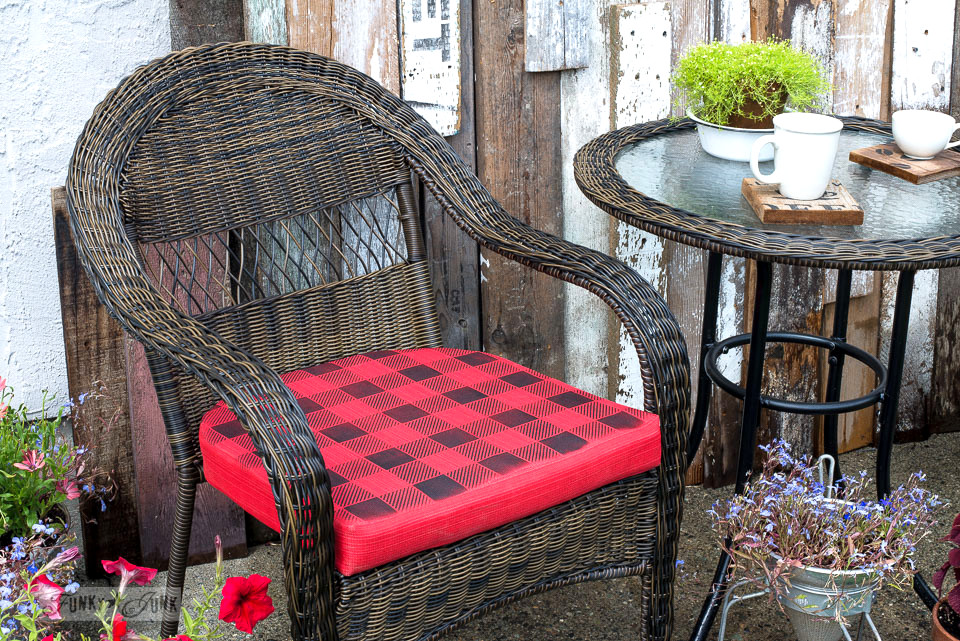 How to Buffalo Check a plain red outdoor cushion to get this charming look instantly! Showcased on this lovely outdoor wicker resin reclaimed wood bistro area. | funkyjunkinteriors.net
