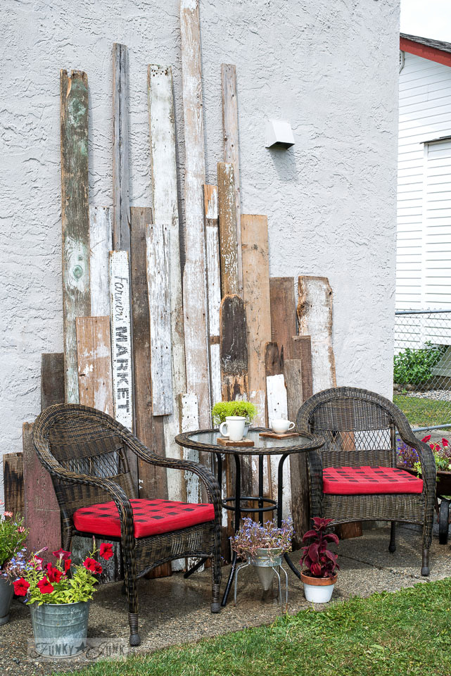 Outdoor wicker resin reclaimed wood bistro area, with DIY buffalo checked red and black chair pads. | funkyjunkinteriors.net