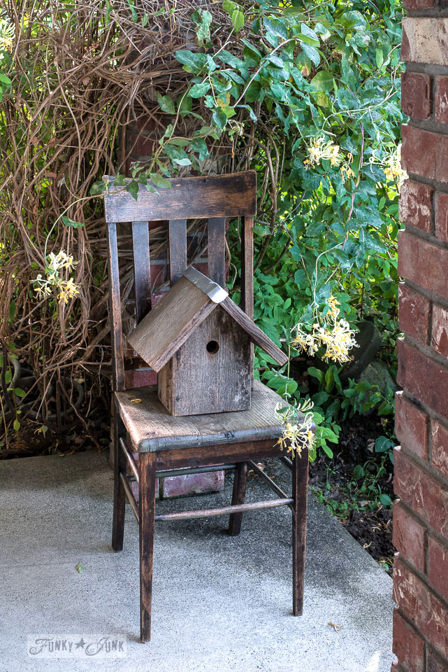 A rustic birdhouse resides on an antique chair, with wisteria as a natural backdrop beside a front door. | funkyjunkinteriors.net
