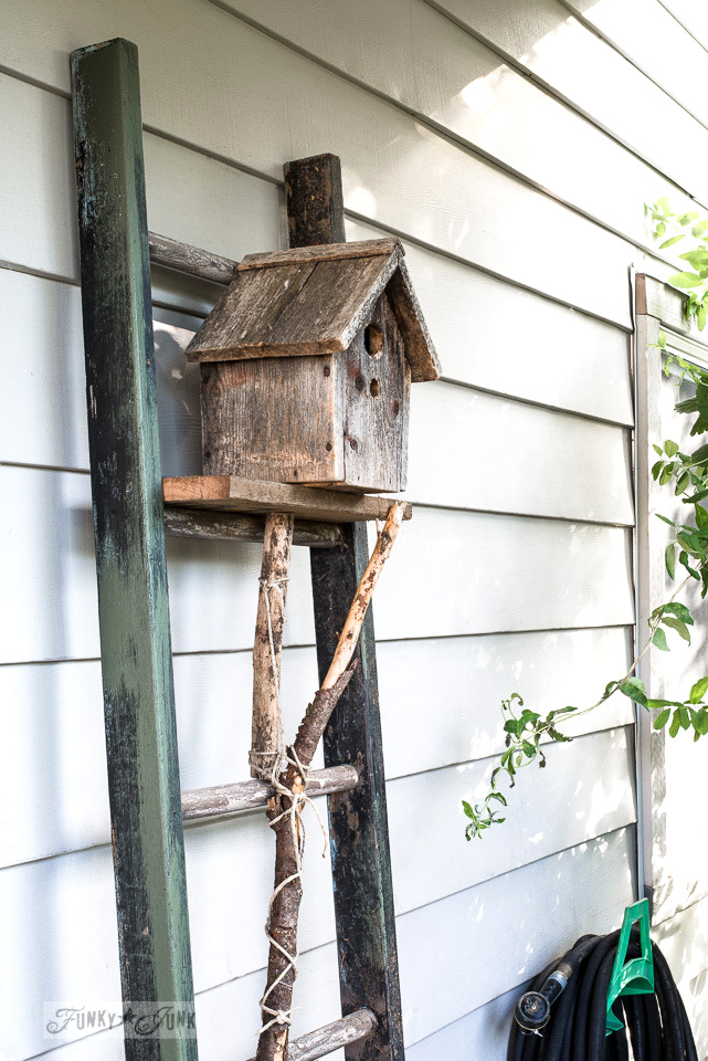 A rustic birdhouse on a reclaimed wood plank shelf, situated on an old painter's ladder held up with branch brackets beside a front door. | funkyjunkinteriors.net
