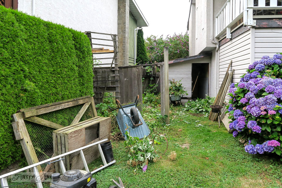 The revamping of a garden shed and reclaimed wood fence in a backyard | funkyjunkinteriors.net