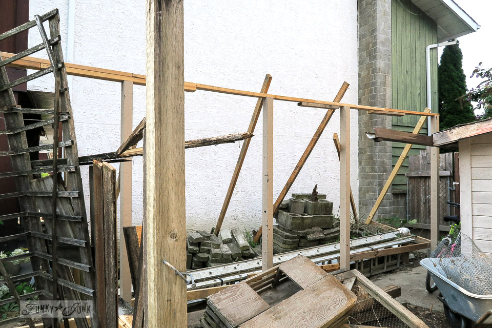 The building of a new fence that will be planked with reclaimed wood in a backyard | funkyjunkinteriors.net