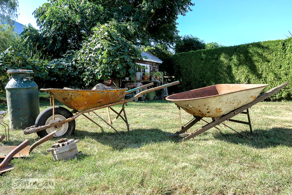 Old wheel barrows and rusty garden junk being grouped in order to be sold | funkyjunkinteriors.net