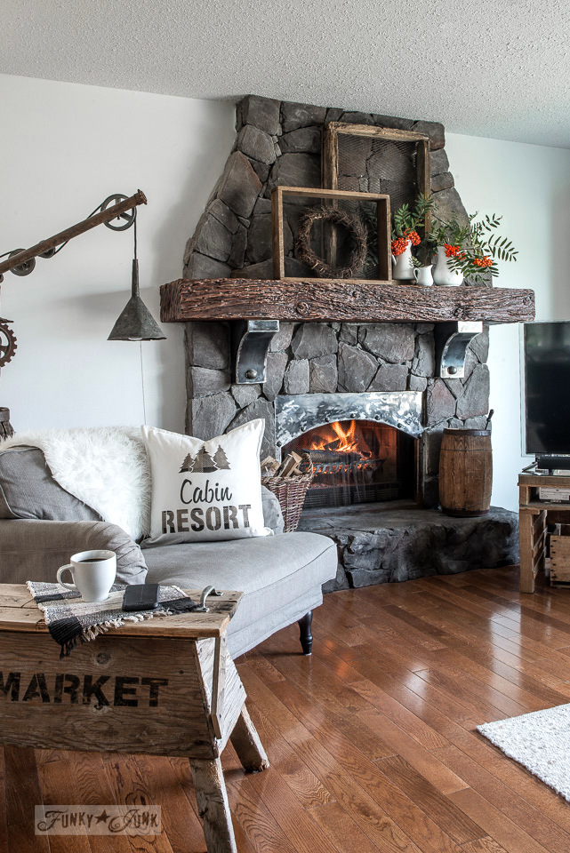 A rustic fall living room with rock fireplace and metal influences, natural branches, antique soil sifters with wreath, and a stenciled cabin resort buffalo checked pillow. Made with Funky Junk's Old Sign Stencils and Fusion Mineral Paint. Tutorial at funkyjunkinteriors.net