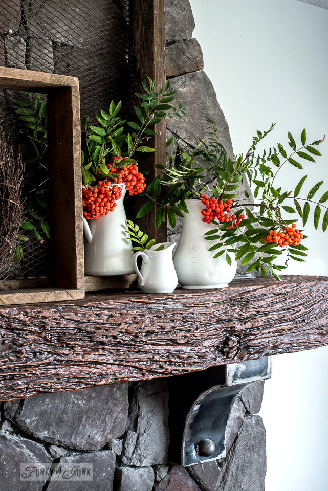 Natural tree branches with orange berries tucked inside 3 white antique pitchers for a fall mantel / funkyjunkinteriors.net