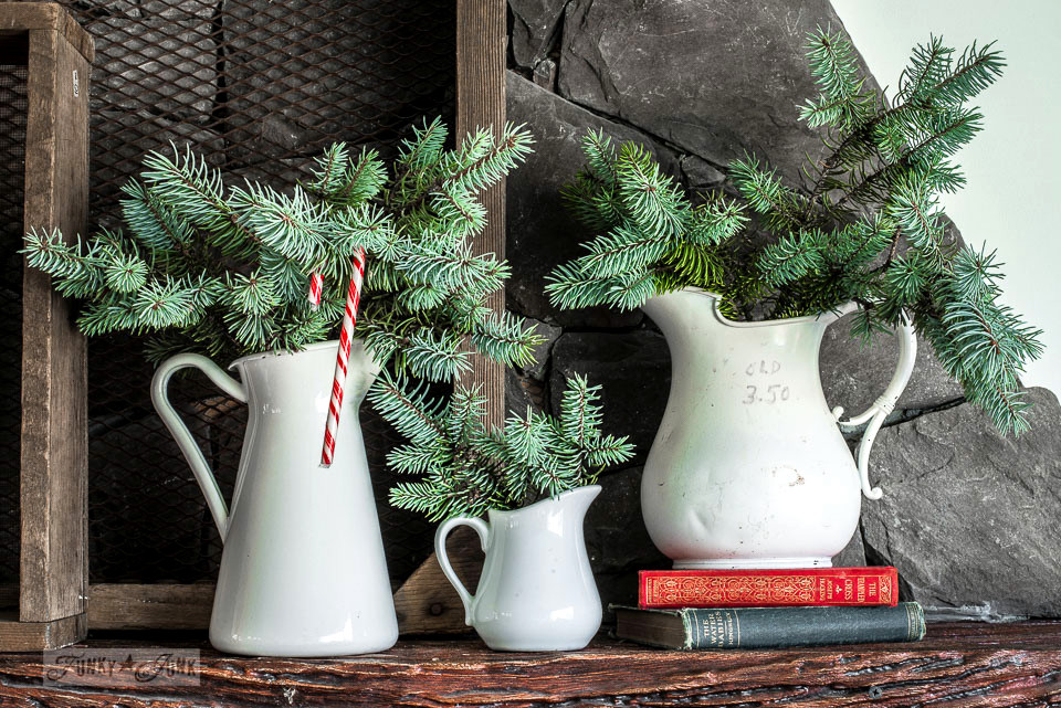 A Christmas mantel of natural Christmas tree branches tucked inside white pitchers / funkyjunkinteriors.net