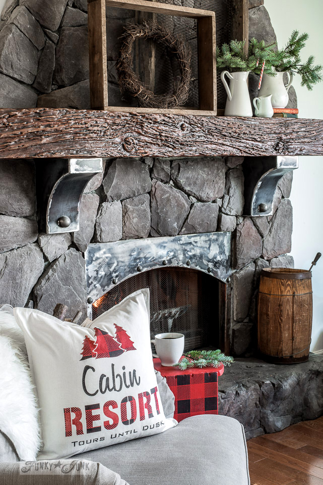 A rustic Christmas living room with rock fireplace and metal influences, natural branches, antique soil sifters with wreath, and a stenciled cabin resort buffalo checked pillow. Made with Funky Junk's Old Sign Stencils and Fusion Mineral Paint. Tutorial at funkyjunkinteriors.net