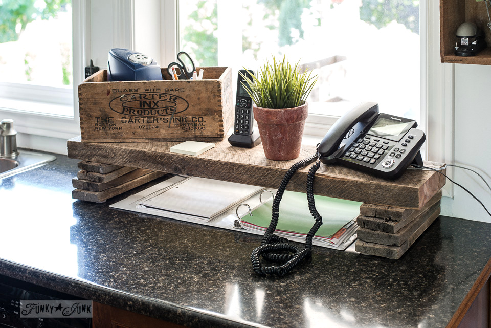 Reclaimed wood shelf for a rustic kitchen phone station with stacked plank risers. | funkyjunkinteriors.net