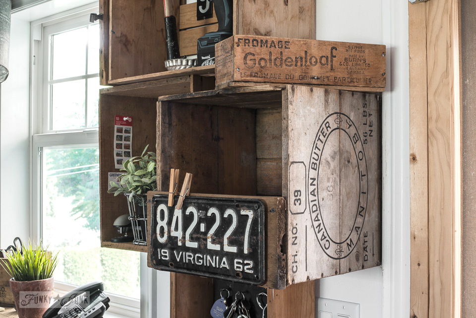 Stacked vintage crates and a reclaimed wood shelf for a rustic kitchen phone station against white walls. | funkyjunkinteriors.net