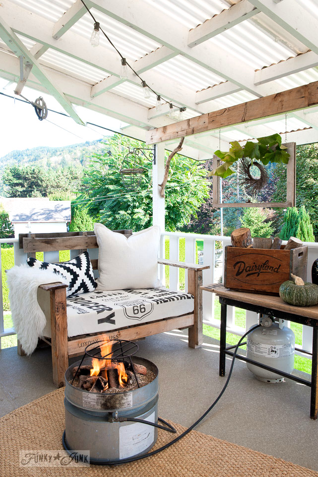 A cozy fall patio setting, decorated with old windows and wreaths, pallet wood furniture and a propane fire pit | funkyjunkinteriors.net