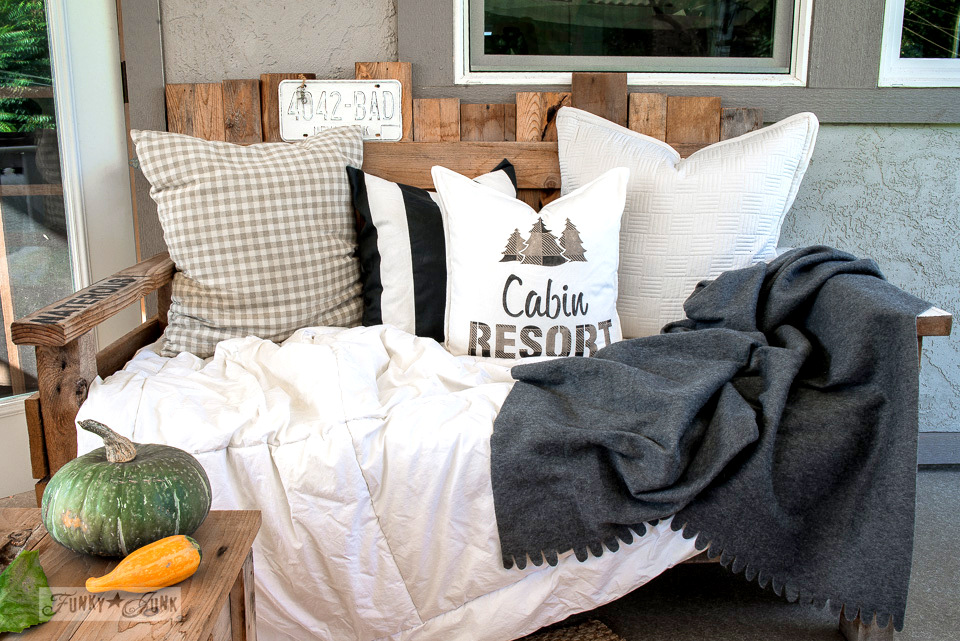 A cozy fall patio setting of a pallet wood sofa filled with blankets and a cabin resort pillow made with Funky Junk's Old Sign Stencils | funkyjunkinteriors.net