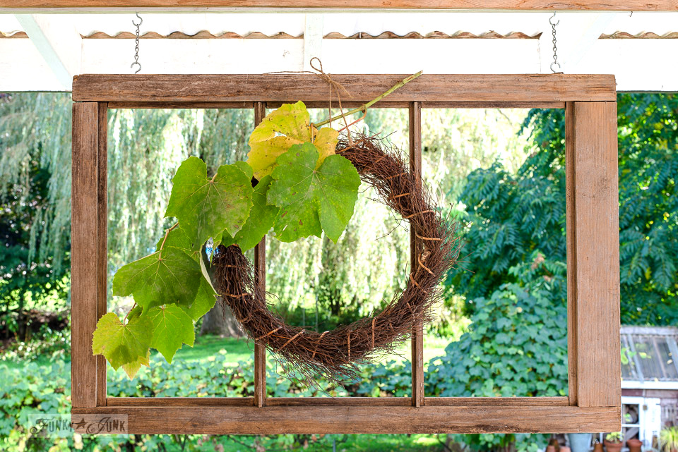 Fall decor on a patio with a wreath hung on old windows | funkyjunkinteriors.net