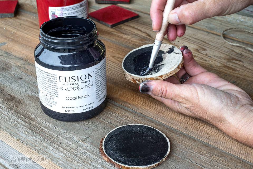 Painting out wood slices with Fusion Mineral Paint's coal black to create snowflake Christmas ornaments with Funky Junk's Old Sign Stencils. Full tutorial at funkyjunkinteriors.net