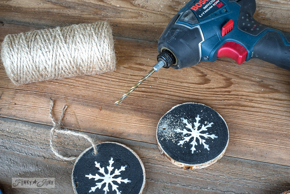 Drilling hanging holes with Bosch drill into wood slice snowflake Christmas ornaments made with Funky Junk's Old Sign Stencils and Fusion Mineral Paint. Full tutorial at funkyjunkinteriors.net