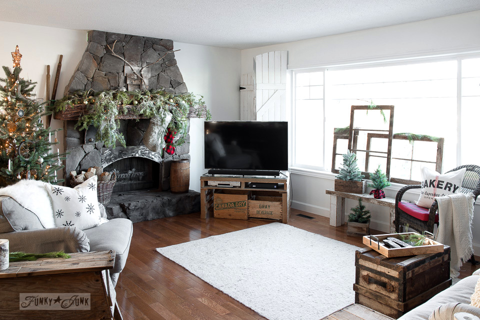 Rustic living room with rock fireplace, pallet wood TV stand, vintage windows, part of Funky Junk's Christmas home tour. See it all at funkyjunkinteriors.net #christmas