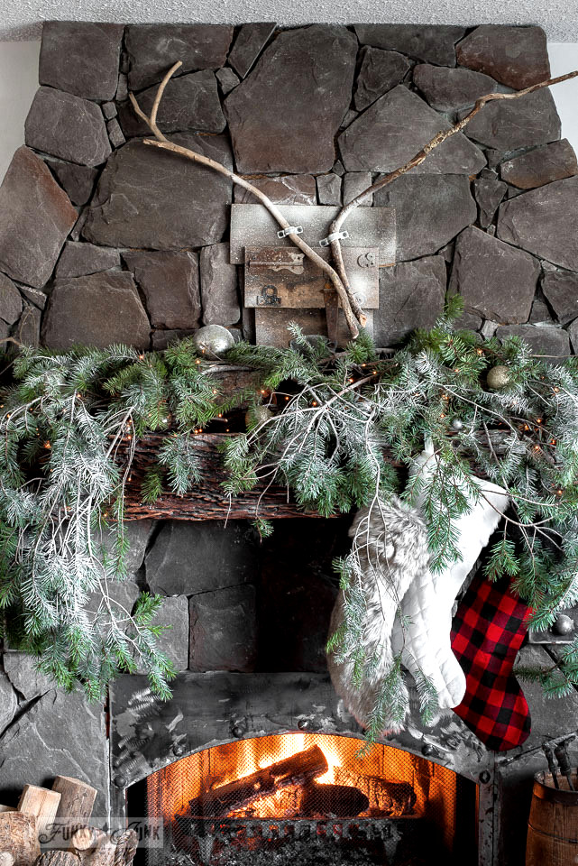 How to create this cozy cabin branch filled Christmas mantel. Complete with reclaimed wood deer head, stockings and fresh fallen snow. Tutorial on funkyjunkinteriors.net #christmasdecor #christmasmantel #christmas #mantel #fireplace