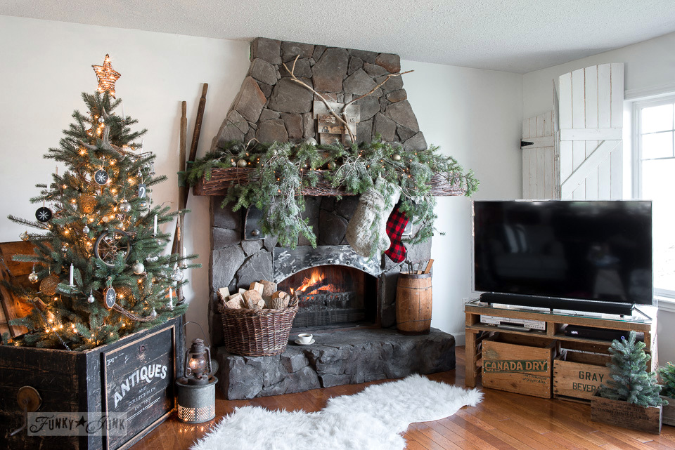 A cozy cabin styled Christmas living room with lots of natural branches. Tutorials on funkyjunkinteriors.net #christmasdecor #christmasmantel #christmas #mantel #fireplace