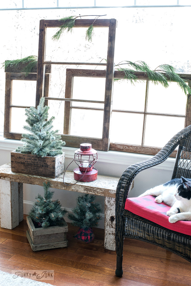 Vintage wood windows bring instant Christmas charm lining a picture window, along with mini Christmas trees and red train lantern | funkyjunkinteriors.net