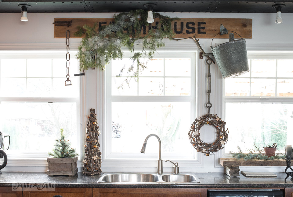 Rustic FARMHOUSE sign as a window valance with evergreen branches and twig Christmas tree and wreath in a kitchen, part of Funky Junk Interiors' Christmas home tour. See it all at funkyjunkinteriors.net #christmas