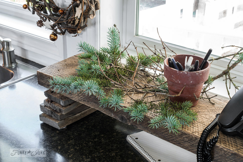 Rustic evergreen branches on a wood scrap kitchen shelf, part of Funky Junk Interiors' Christmas home tour. See it all at funkyjunkinteriors.net #christmas