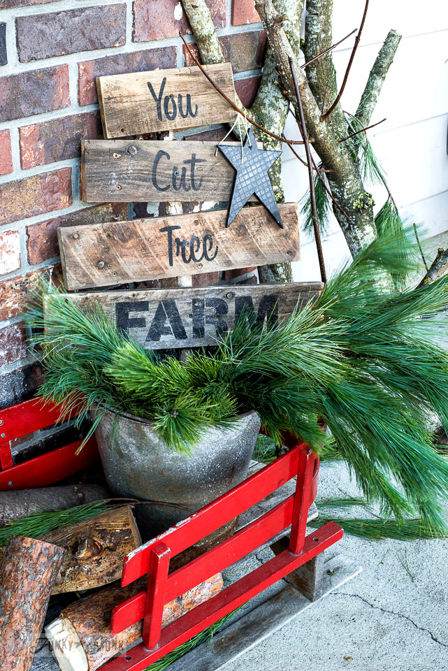 A festive tree farm themed Christmas front porch, infused with branches, a sage green door and a tree farm sign in a wooden sleigh. Made with Funky Junk's Old Sign Stencils and Fusion Mineral Paint \ tour at funkyjunkinteriors.net