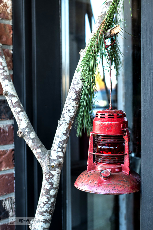 A red train lantern hanging within a festive tree farm themed Christmas front porch, infused with branches, a sage green door and a tree farm sign in a wooden sleigh \ tour at funkyjunkinteriors.net