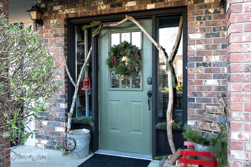 A festive tree farm themed Christmas front porch, infused with branches, a sage green door and a tree farm sign in a wooden sleigh \ tour at funkyjunkinteriors.net