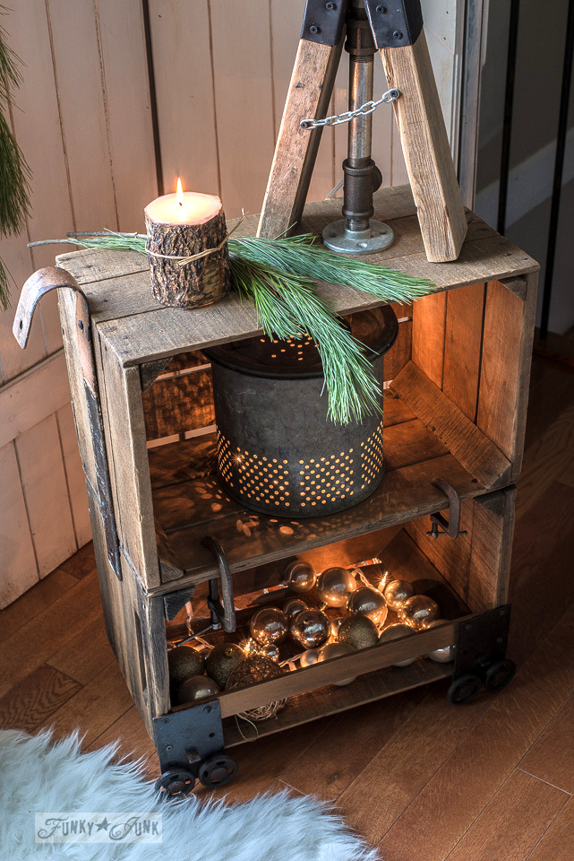 Faux industrial cart coffee crate side table illuminated for Christmas with a vintage bait bucket, ornaments and white mini lights. | funkyjunkinteriors.net #christmas #crates #rustic #furniture #funkyjunk