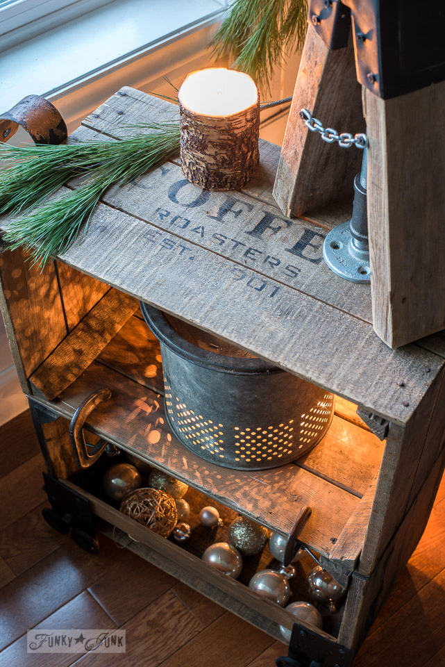Faux industrial cart coffee crate side table illuminated for Christmas with a vintage bait bucket, ornaments and natural greens | funkyjunkinteriors.net #christmas #crates #oldsignstencils