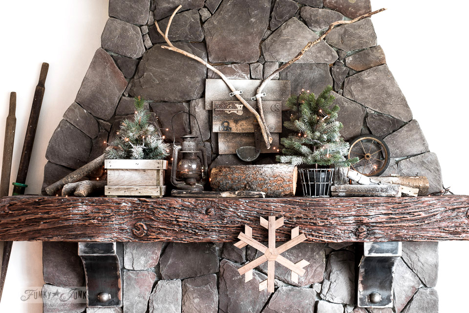 Winter rock fireplace mantel with mini trees, firewood, snow and a reclaimed wood deer head. Part of Rustic winter decorating with black, white and wood. Full tour on funkyjunkinteriors.net