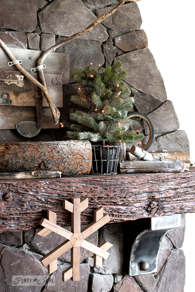 Winter rock fireplace mantel with mini trees, firewood, snow and wooden snowflake. Part of Rustic winter decorating with black, white and wood. Full tour on funkyjunkinteriors.net