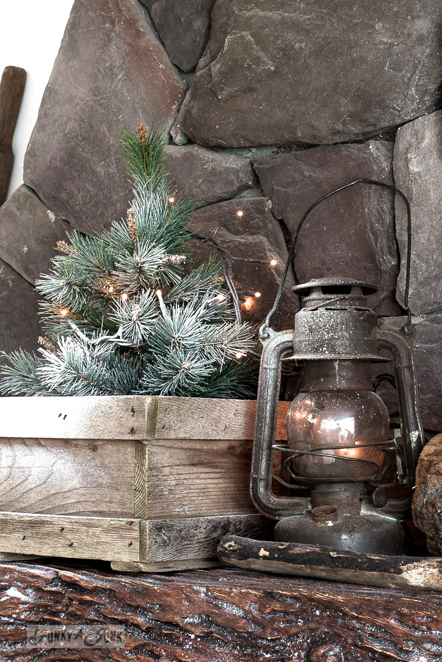 Winter rock fireplace mantel with mini trees, firewood, snow and antique lantern. Part of Rustic winter decorating with black, white and wood. Full tour on funkyjunkinteriors.net