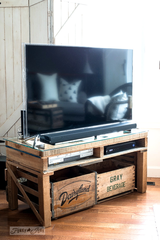 A rustic pallet and vintage crate TV media stand for a big screen TV.