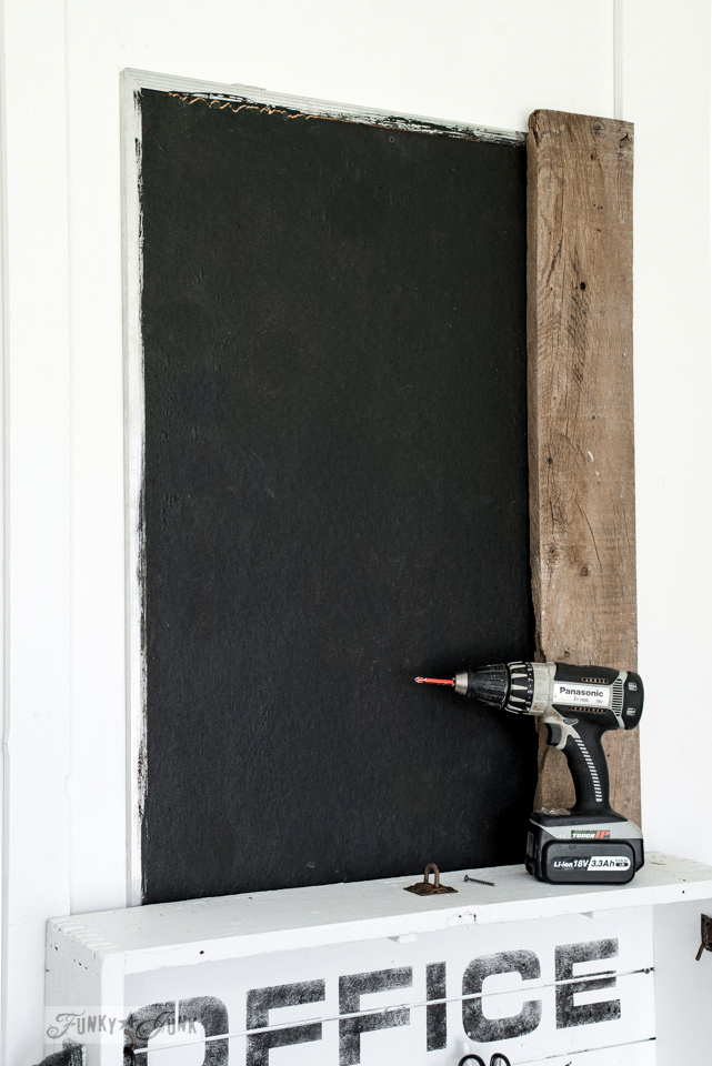 Attaching a painted bulletin board to the wall, and framing it with reclaimed wood