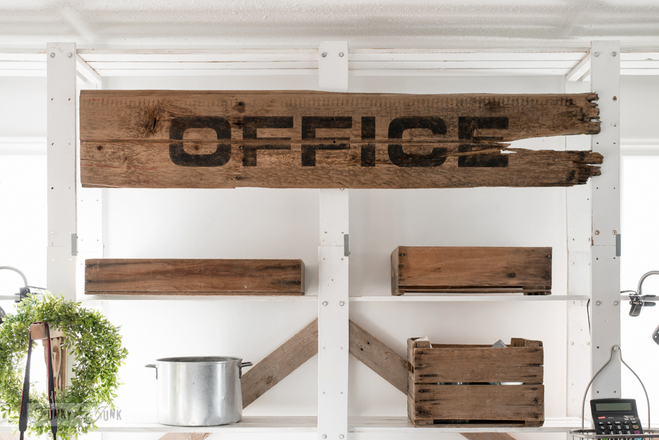 Pallet wood office desk with large sign and rustic benches, including crates for paperwork organizing. With Funky Junk's Old Sign Stencils and Fusion Mineral Paint. Click to visit on Funky Junk Interiors. #funkyjunkinteriors #oldsignstencils #fusionmineralpaint #office #signs #rustic #reclaimed #reclaimedwood #farmhouse #farmhousestyle